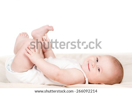 Portrait of a cute 3 months baby lying down on a blanket. Feeling dry and happy. Happy little baby smiling while laying on white background - stock photo