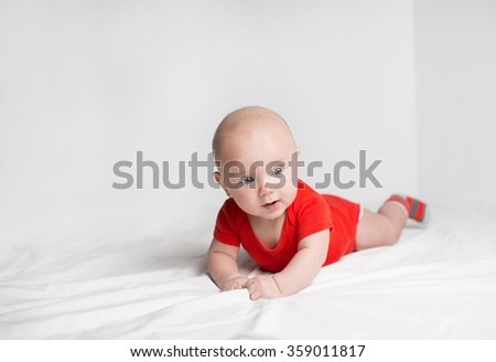 Portrait of a cute 5 months old baby boy in a red onesie lying down on a white blanket, looking aside