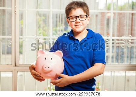 Portrait of a cute nerdy boy carrying a piggy bank with his savings and smiling - stock photo