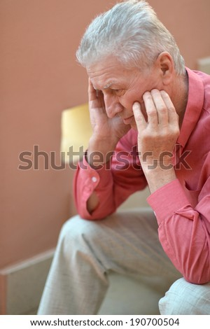Portrait of a cute old thoughtful man on red wall background