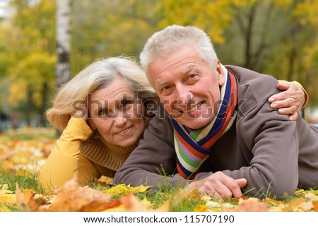 portrait of a cute older couple lying in autumn park