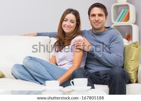 Portrait of a cute relaxed young couple sitting on sofa at home