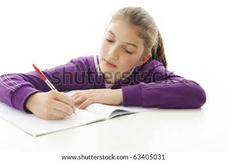 Portrait of a cute school girl at her desk - stock photo