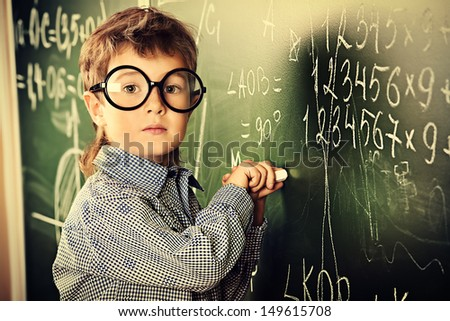Portrait of a cute schoolboy in round glasses writing on a blackboard in a classroom.