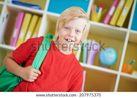 Portrait of a cute schoolboy with backpack looking at camera - stock photo