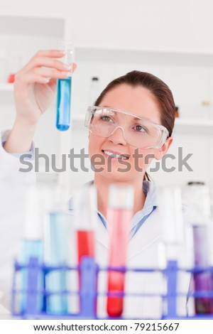 Portrait of a cute scientist looking at test tubes