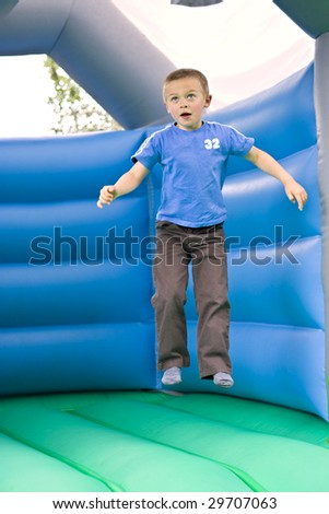 Portrait of a cute six year old boy jumping on a bouncy castle moonwalk - stock photo