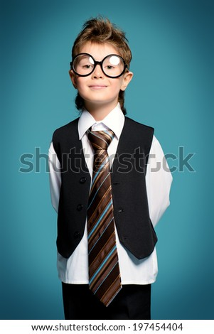 Portrait of a cute smart boy wearing suit and spectacles. Education. Studio shot. - stock photo