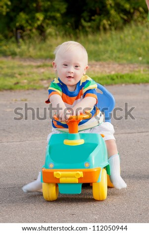 Portrait of a cute smiling baby boy with Down syndrome who driving a toy car - stock photo