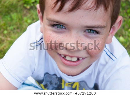 Portrait of a cute smiling boy with freckles