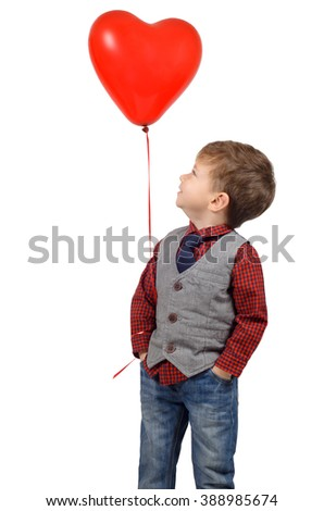 Portrait of a cute smiling little boy holding a red heart shaped balloon isolated on white background