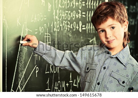 Portrait of a cute smiling schoolboy writing on a blackboard in a classroom. - stock photo