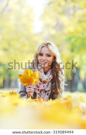 Portrait of a cute smiling woman lying in autumn leaves in park - stock photo