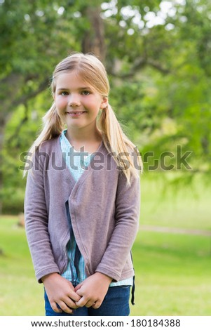 Portrait of a cute smiling young girl standing at the park