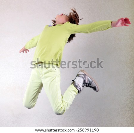 Portrait of a cute sportive, cheerful happy girl jumping and dancing. Childhood, freedom, happiness concept. - stock photo
