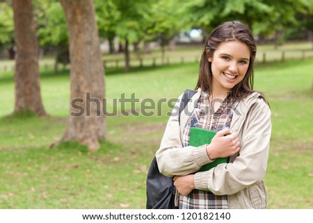 Portrait of a cute student holding textbook while posing in a park - stock photo