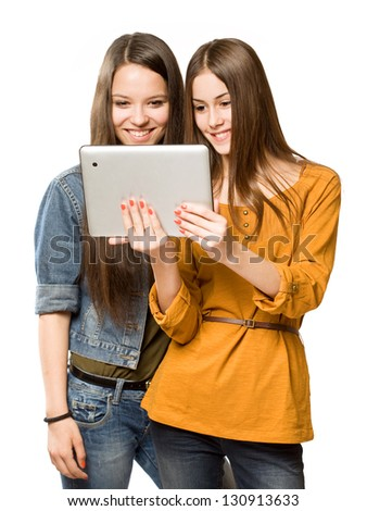 Portrait of a cute teen girls sharing a tablet computer.
