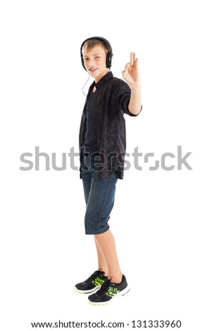 Portrait of a cute teenage boy wearing a black shirt, denim shorts and sneakers with headphones on his shoulders. The boy showing OK sign. Studio shot, isolated on white background. - stock photo