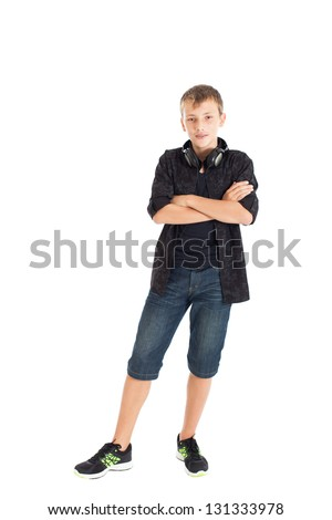 Portrait of a cute teenage boy wearing a  black shirt, denim shorts and sneakers with headphones on his shoulders. Folded his arms across his chest. Studio shot, isolated on white background. - stock photo