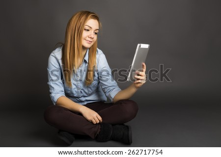 Portrait of a cute teenage using a digital tablet while sitting on the floor over gray background - stock photo