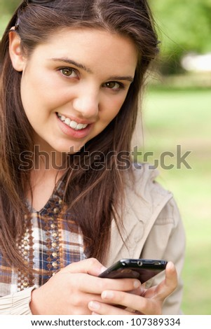 Portrait of a cute teenager using a smartphone in a park - stock photo