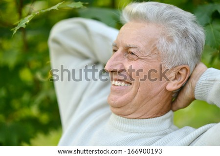 Portrait of a cute thoughtful old man at nature
