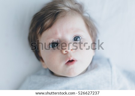 Portrait of a cute three months old baby lying on the white blanket and looking to the camera