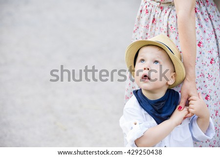 Portrait of a cute toddler boy on straw hat holding his mother's hand and looking at the sky. Adorable child with his mom walking in the park. Together. Childhood and lifestyle concept - stock photo
