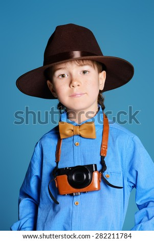 Portrait of a cute 7 year old boy in elegant hat and bow-tie making photographs by his camera. Occupations. - stock photo