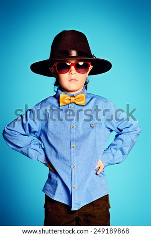 Portrait of a cute 7 year old boy wearing elegant hat and bow-tie with sunglasses.  - stock photo