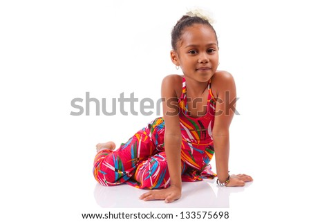 Portrait of a cute young African Asian girl seated on the floor - stock photo