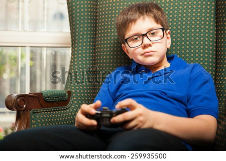 Portrait of a cute young boy holding a video game controller at home - stock photo