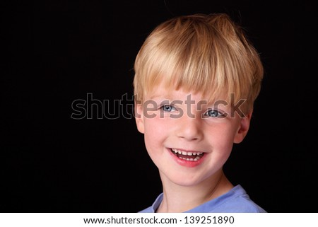 Portrait of a cute young boy on black background - stock photo
