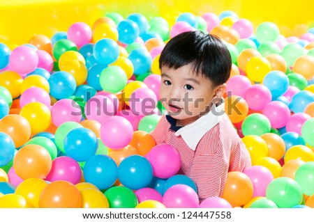 Portrait of a cute young boy sitting in ball pit.