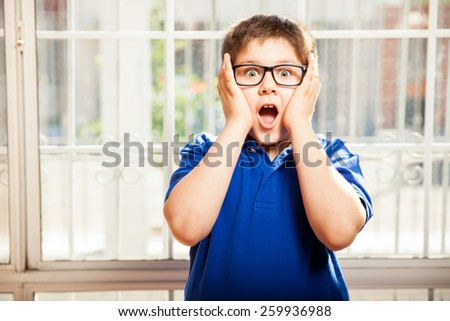 Portrait of a cute young boy with glasses looking shocked and surprised about something - stock photo
