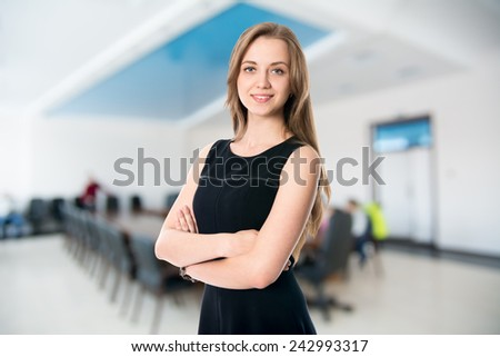 Portrait of a cute young business woman smiling, in an office environment.