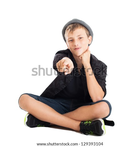Portrait of a cute young European guy. The guy wearing fashionable clothes and hat sitting on the floor. It shows the index finger forward. Studio shot, isolated on white background. - stock photo