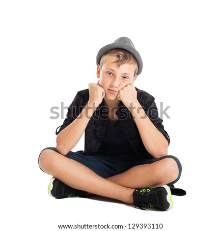Portrait of a cute young European guy. The guy wearing fashionable clothes and hat sitting on the floor. Serious thoughtful face. Studio shot, isolated on white background. - stock photo