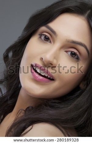 Portrait of a cute young female smiling over colored background - stock photo