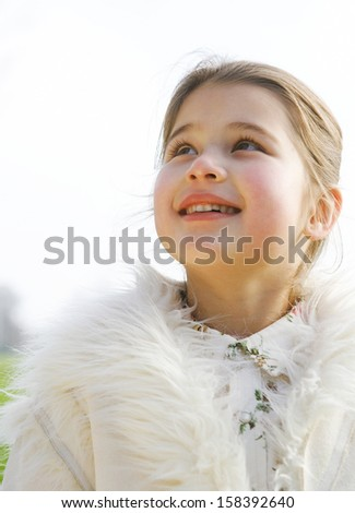 Portrait of a cute young girl child smiling and being joyful while in a park during a sunny winter day, looking up to the sky and wearing a warm coat, outdoors. - stock photo