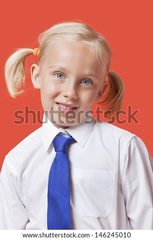 Portrait of a cute young girl in school uniform over blue background - stock photo
