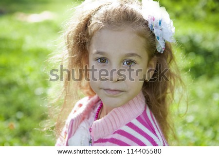 portrait of a cute young girl looking into the camera with a smile on her face - stock photo