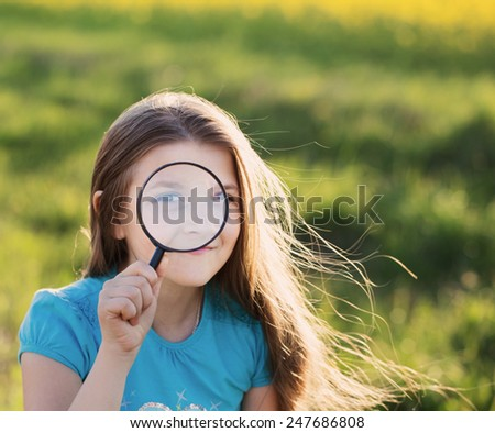 portrait of a cute young girl looking through magnifying glass - stock photo