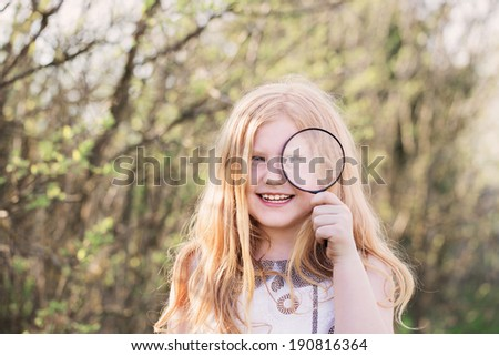portrait of a cute young girl looking through magnifying glass at the park - stock photo