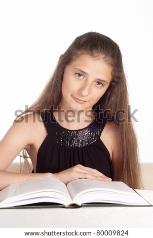 portrait of a cute young girl reading a book