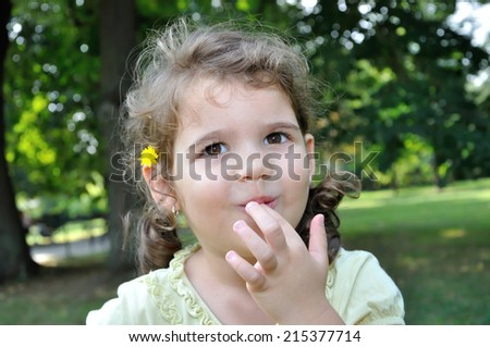 Portrait of a cute young girl with finger in her mouth - stock photo