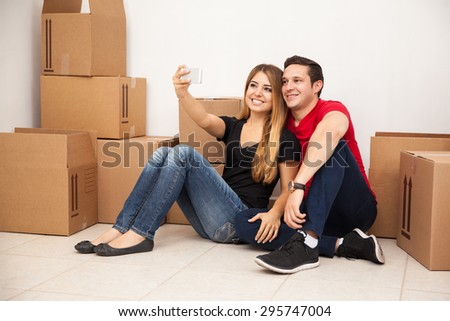Portrait of a cute young Hispanic couple taking a selfie with a smartphone while moving to their new apartment - stock photo