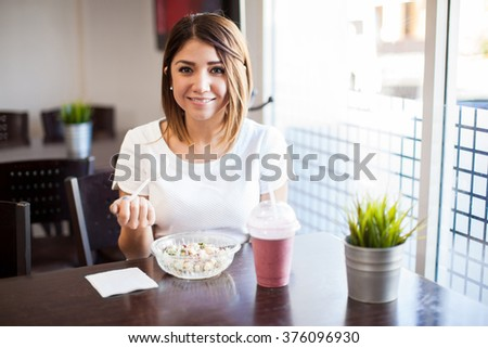 Portrait of a cute young Hispanic woman eating a salad and drinking a smoothie at a restaurant - stock photo