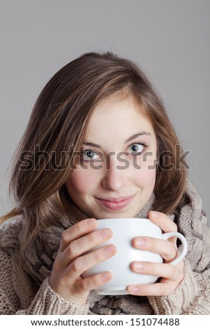 Portrait of a cute young lady in the winter with a cup of tea.  - stock photo