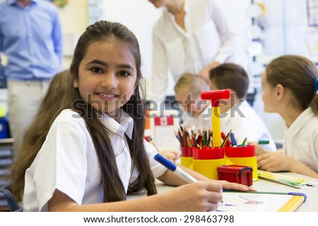 Portrait of a cute young schoolgirl smiling at the camera while sitting at her desk. - stock photo